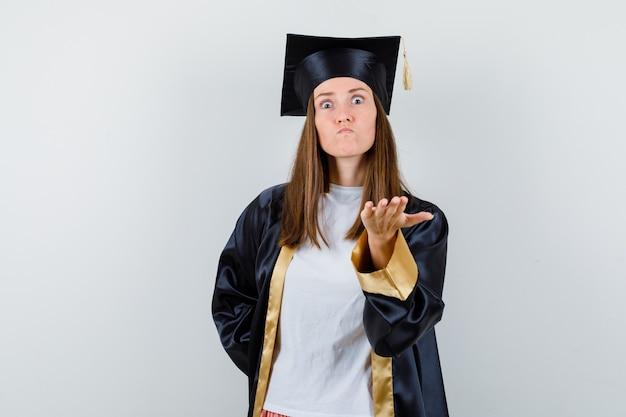 Femme diplômée en uniforme, vêtements décontractés, étirant la main dans le geste de questionnement et à la colère, vue de face.