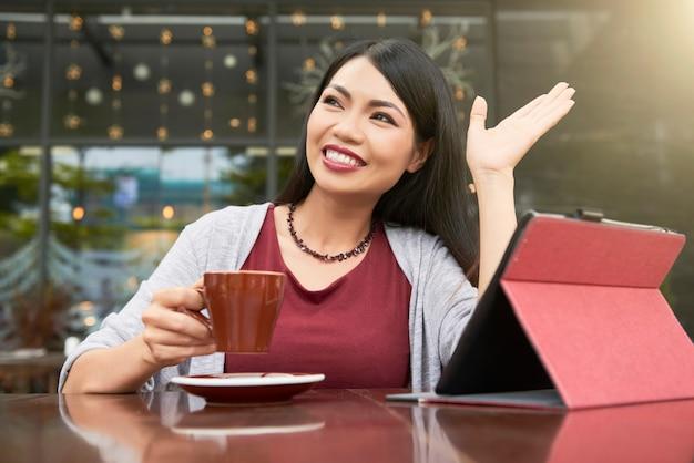 Femme disant bonjour au café