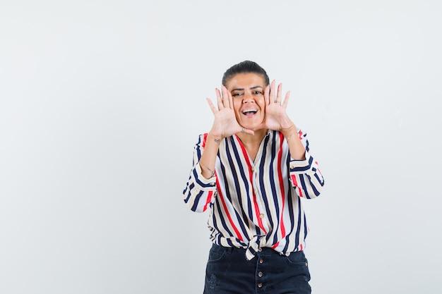 Femme disant secret ou annonçant quelque chose en chemise, jupe et à la recherche positive
