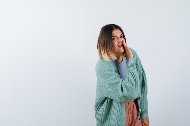 Femme disant secret derrière la main dans des vêtements décontractés et à la curieuse, vue de face.