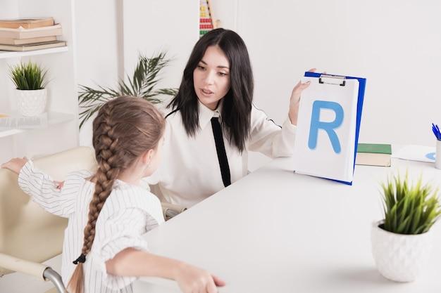 Femme avec un discours de formation de fille d'enfant ensemble assis dans la salle blanche.