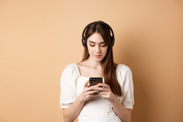 Femme discutant sur téléphone portable et écoutant de la musique dans des écouteurs sans fil debout sur fond beige