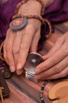 Une femme diseuse de bonne aventure tient une boule du destin dans ses mains, une boule magique de prédictions