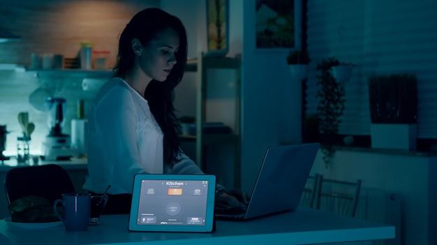 Femme à distance travaillant dans une maison moderne donnant une commande vocale à une tablette avec une application de maison intelligente et des lumières allumées