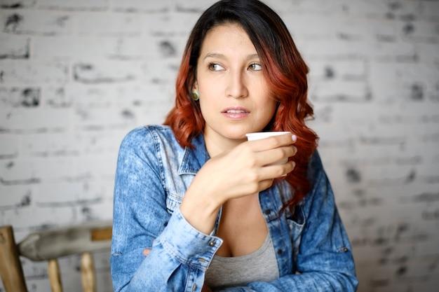 Femme distraite aux cheveux rouges tient une tasse blanche