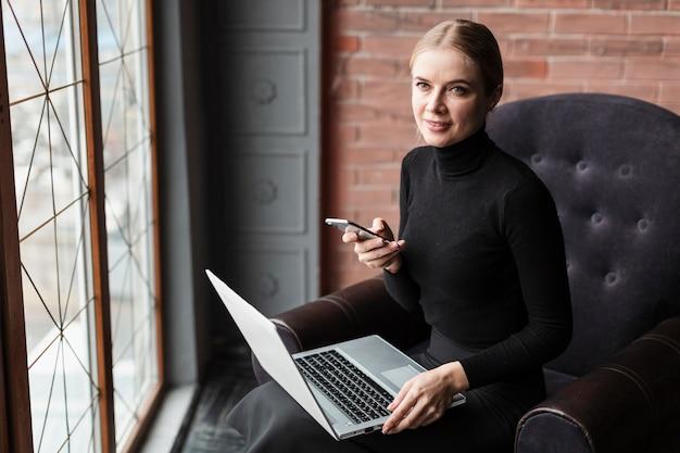Femme, divan, ordinateur portable, mobile