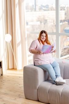 Femme dodue positive lisant sur les tendances de la mode moderne assise sur le canapé