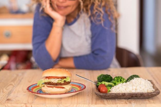 La femme doit choisir entre un hamburger ou des légumes et se lever pour avoir une bonne hygiène de vie et être heureuse d'elle-même - l'homme choisit le type de nourriture qu'il préfère