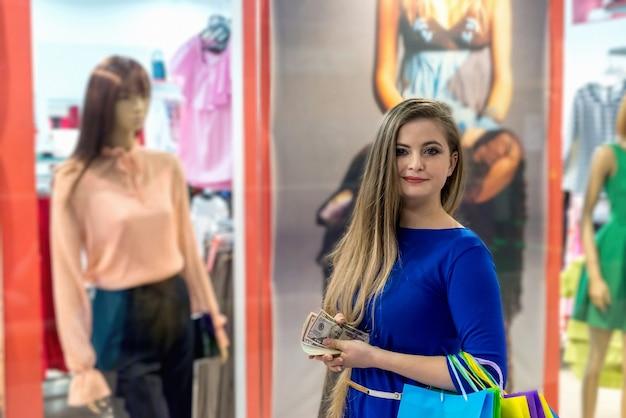 Femme avec des dollars et des sacs près de la vitrine