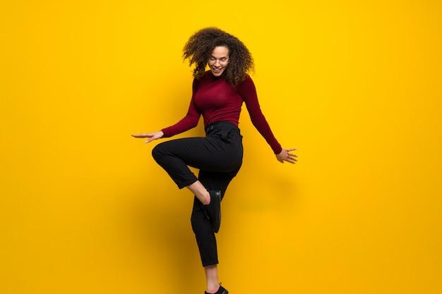Femme dominicaine aux cheveux bouclés sautant par-dessus un mur jaune isolé