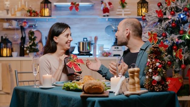 Femme donnant une boîte à un homme tout en profitant du dîner de noël