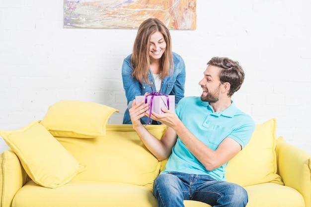 Femme donnant un cadeau surprise à son petit ami heureux assis sur un canapé