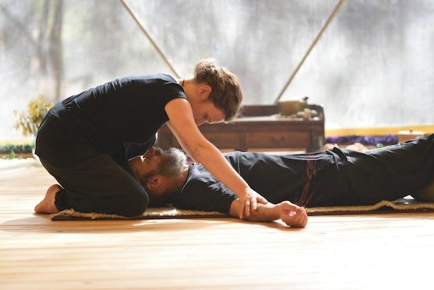 Femme donnant un massage tantrique à son partenaire sur un tapis