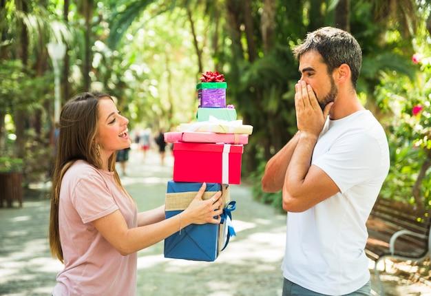 Femme donnant une pile de cadeaux à son petit ami surpris