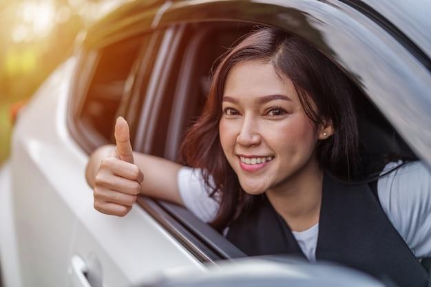 Femme donnant le pouce à l'intérieur de sa voiture