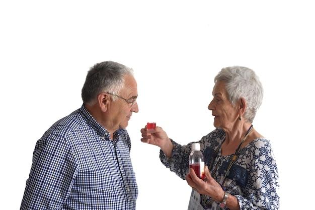 Une femme donnant à son partenaire des médicaments sur fond blanc
