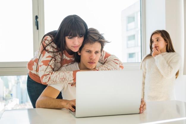 Femme donnant un soutien à son mari travaillant sur ordinateur portable à la maison