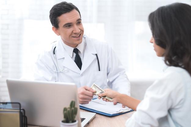 Une femme donne de l'argent à un médecin dans son bureau.