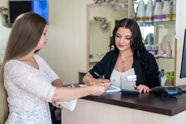 Femme donne des billets en euros à l'administrateur dans un salon de beauté