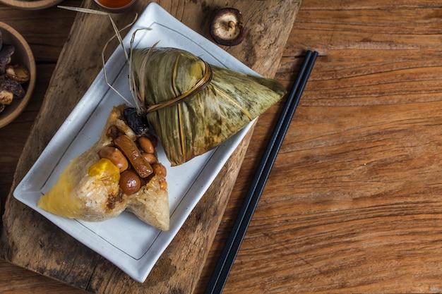 Une femme donne du zongzi (boulette de riz) à d'autres comme cadeau du festival du bateau-dragon