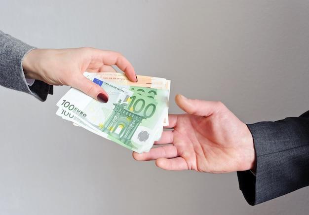 Une femme donne à un homme des billets en euros