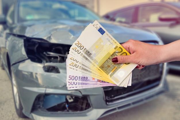 Une Femme Donne Un Mécanicien Euro Pour Réparer Sa Voiture Cassée. Photo Premium