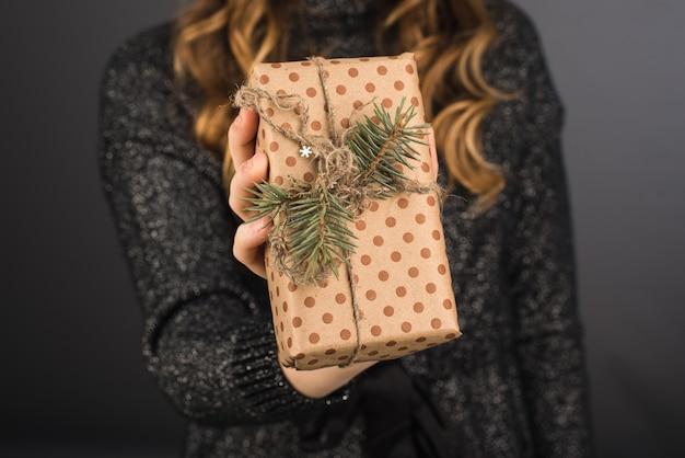 Femme donne un paquet dans un emballage artisanal avec une branche de rameau