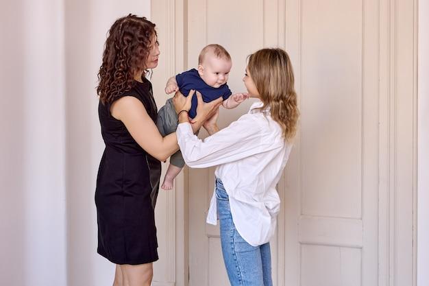 Une femme donne son enfant à une baby-sitter alors qu'elle se tient à l'intérieur
