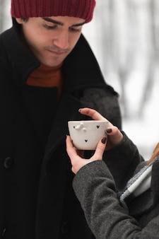 Femme, donner, chaud, tasse thé, à, elle, petit ami