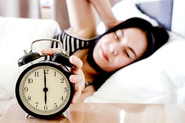 Femme dormant et réveil dans la chambre à la maison