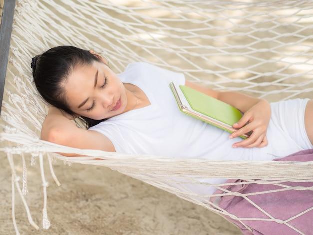 Femme, dormir sur un hamac avec tablette sur la plage