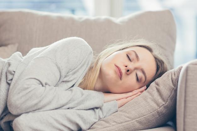 Une femme dort au repos à la maison sur un canapé après une dure journée