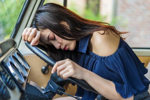 Femme dort dans la voiture vintage