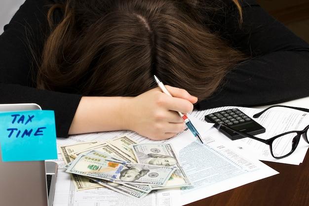 La femme dort sur la déclaration de revenus individuelle.
