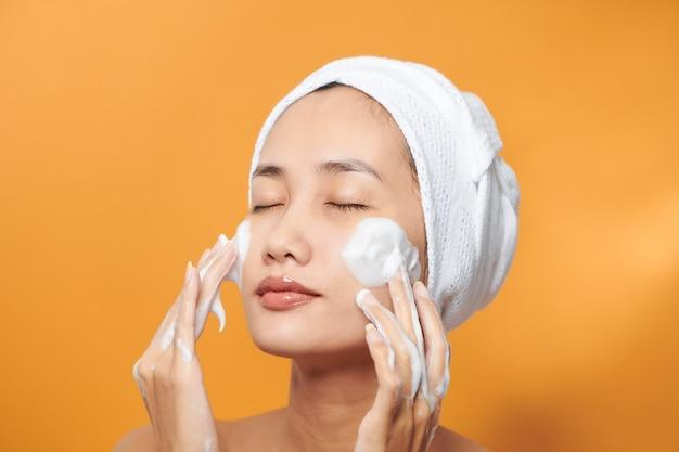 Femme douce à moitié nue enveloppée dans une serviette se lavant le visage avec un nettoyant moussant isolé sur fond orange