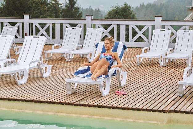 Femme douce, profitant des vacances d'été, allongée sur une chaise de plage.