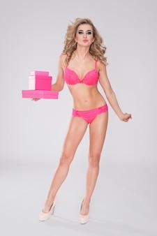 Femme douce et sexy en lingerie tenant des cadeaux roses