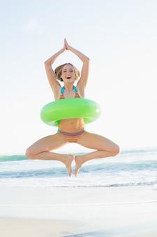 Femme douce tenant une bague en caoutchouc sautant sur la plage