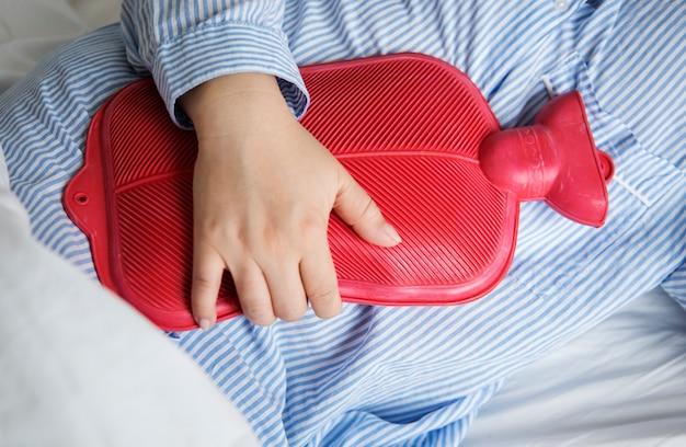 Une femme en douleur tenant une bouteille d'eau chaude