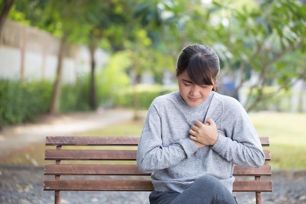 La femme a des douleurs thoraciques au parc