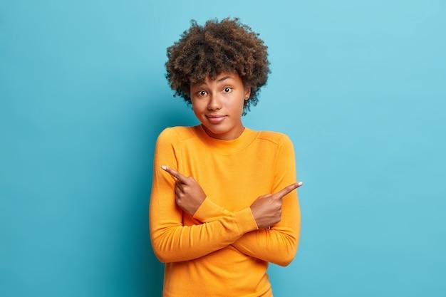 Une femme douteuse croise les bras et pointe de différents côtés hésite entre deux articles ou variantes porte un pull orange pose contre un mur bleu a besoin d'aide pour prendre des décisions à l'intérieur