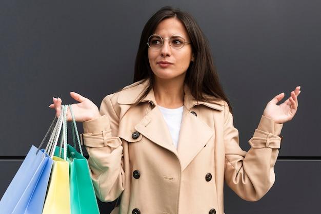 Femme douteuse à l'extérieur tenant beaucoup de sacs à provisions