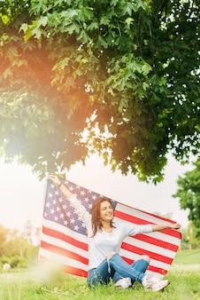 Femme avec drapeau américain assis sous l'arbre