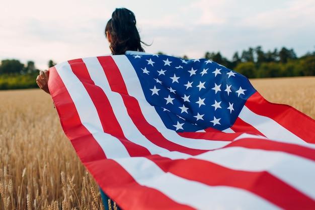 Femme avec drapeau américain dans le champ de blé au coucher du soleil