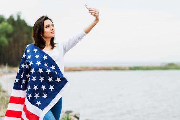 Femme avec drapeau américain prenant selfie au lac