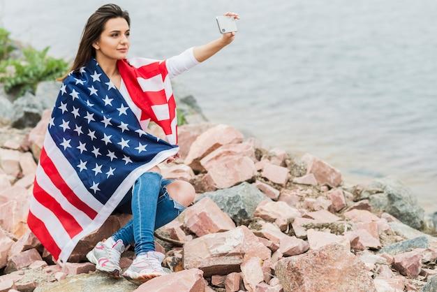 Femme avec drapeau américain prenant selfie à côté de l'eau
