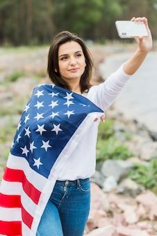 Femme avec drapeau américain prenant selfie dans la nature