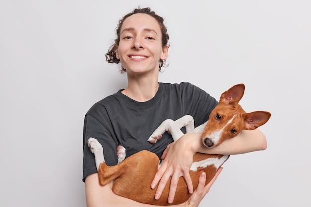 Femme dresseur porte chien basenji aime passer du temps libre avec animal domestique devient animal domestique comme présent va former chiot se dresse sur blanc