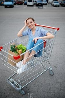 Femme drôle assise dans le panier sur le parking du supermarché. client heureux avec des achats dans le centre commercial, véhicules en arrière-plan