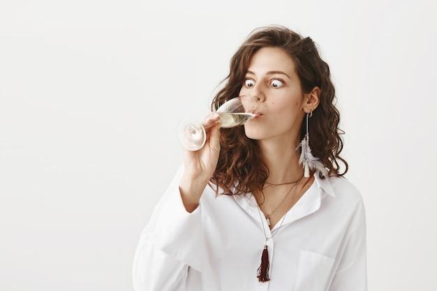 Femme drôle avaler du champagne dans un verre